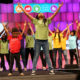 Children in colorful t-shirts and jeans onstage