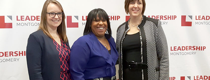 3 woman smiling in front of a Leadership Montgomery backdrop