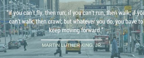 """A city street with the MLK Jr. quote """"If you can't fly, then run; if your can't run, then walk; if you can't walk, then crawl; but whatever you do, you have to keep moving forward."""""""