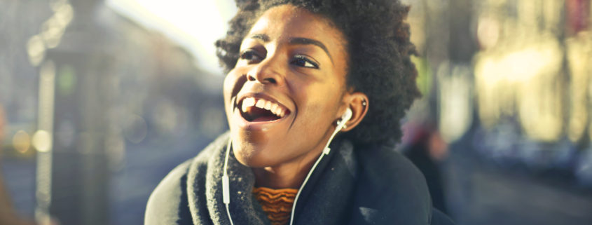 a Black woman in a winter coat and scarf with earbuds singing along and smiling