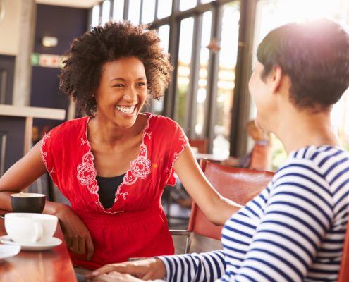 Two women smiling and talking over a coffee