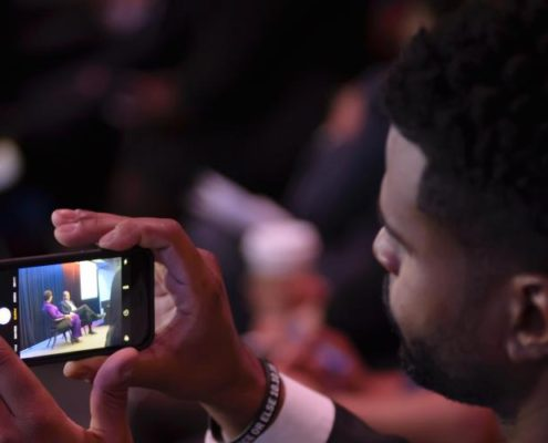 A man holding a smart phone taking video of speakers onstage