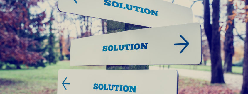 A sign post with signs pointing in multiple direction that all say SOLUTION