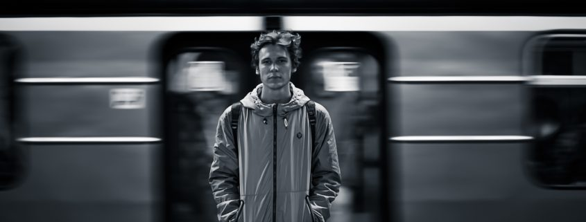 a young man looking directly at the camera as a subway train speeds behind him