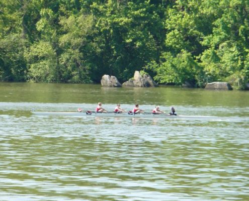 A group of women on a crew team rowing on the Anacostia river