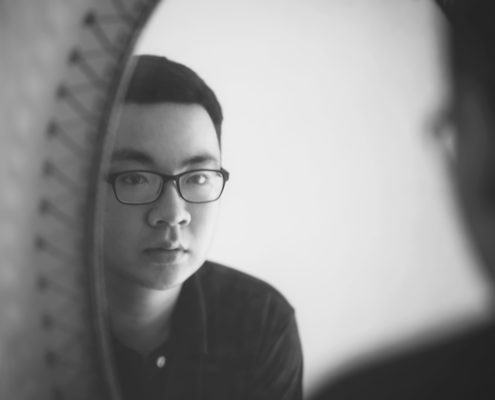 the reflection of a young man with glasses in a mirror