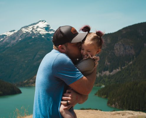 adult holding a child and giving them a hug in front of a picturesque mountain landscape
