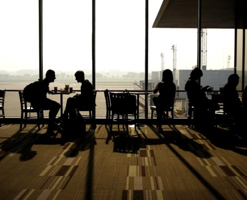 People talking in small groups silhouetted against a large window