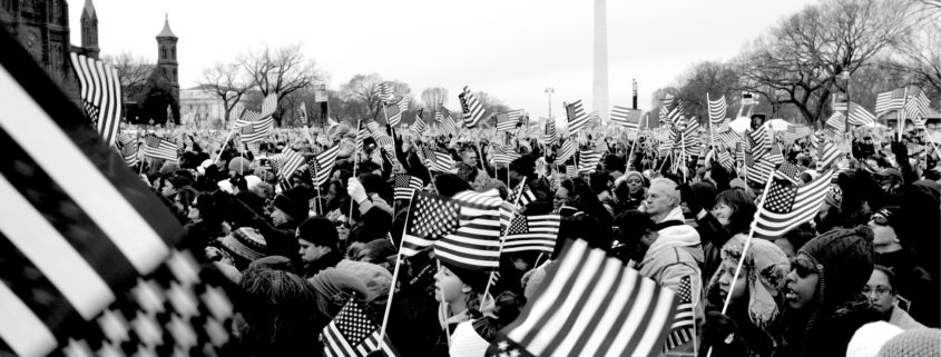 A crowd of people on the Mall in Washington, DC waving American flags. The Washington Monument is in the background.