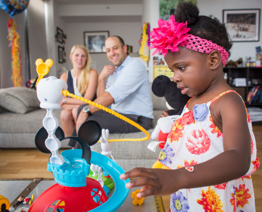 A young Black girl playing with a brightly colored toy set with her adoptive parents in the background