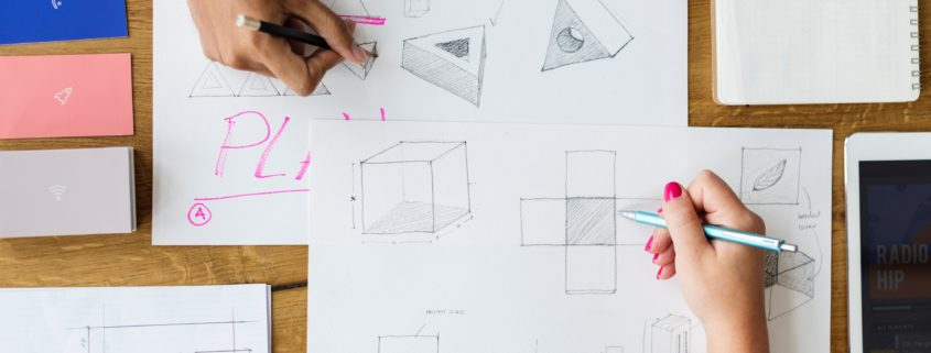 A top down view of sketches laid out on a table with two people working on them