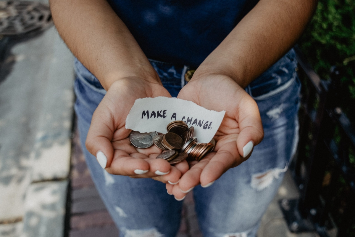"""a woman's hand holding coins with a scrape paper reading """"Make A Change"""""""