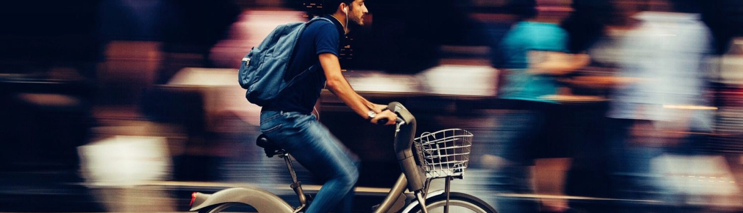 A man in jeans and a t-shirt, with a backpack and headphones, riding a bicycle. The background of people behind him in blurred