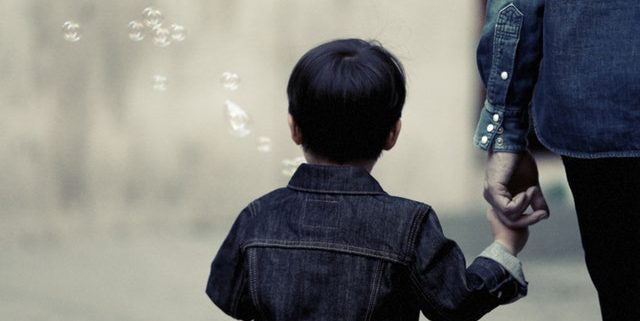 the back of a child holding an adult's hand with bubbles in the air