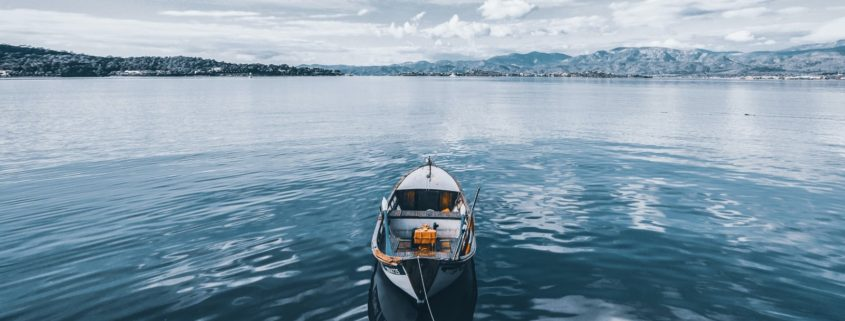 Row boat floating in the middle of water under blue skies with mountains in the background