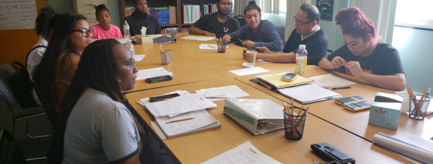 A group of students sit around a conference table, learning from Carolyn Lowery