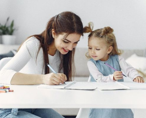 Mom and young daughter writing together