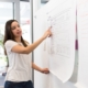 A young women leading strategy planning meeting and pointing to whiteboard diagram