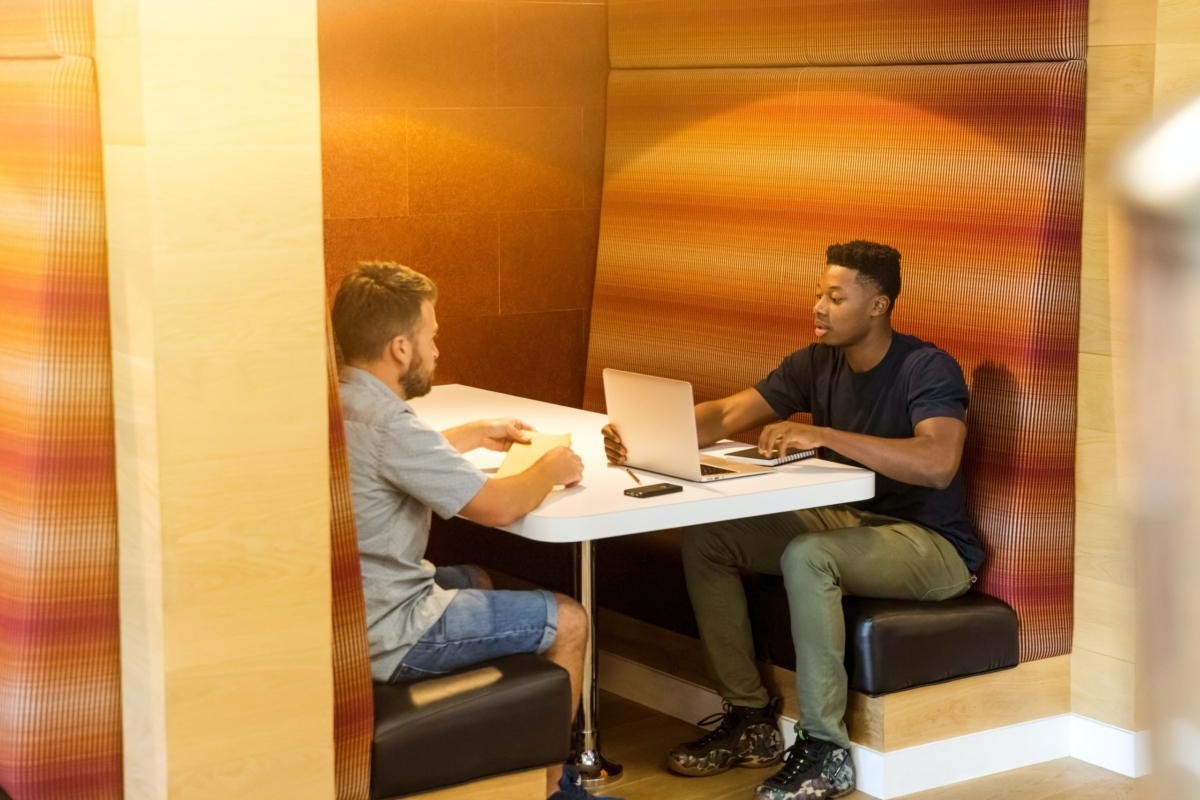 White man and black man working together in a booth. The black man has a laptop