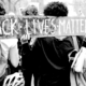 A black and white photo of protestors from behind holding a sign that says BLACK LIVES MATTER