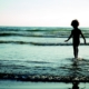 child walking into the waves on the beach