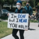 """Protester with a face mask holding sign that says """"I'm Deaf But I Hear You #BLM"""""""