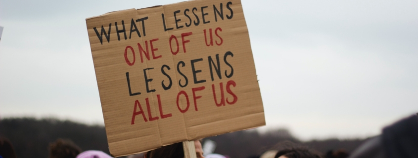 Cardboard protest sign reading What lessens one of us lessens all of us