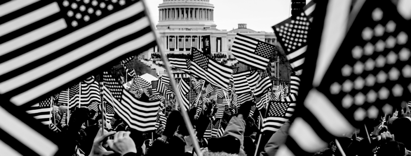 Rally of people in Washington DC with American Flags. The Capital Building is in the distance